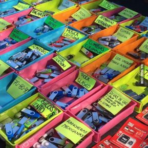 """A photograph of a seller illegally selling music on USB flash drives at a street market in Mexico. It is interesting to see in the comments section people's reaction to the image. There are sceptical readers commenting """"Don't buy it. Just don't. They are probably filled with so many viruses, all your passwords will be known to him soon."""", and others are praising the idea; """"GOD BLESS PIRACY"""". It's interesting how the flash drives are more related to malware as opposed to when pirated music used to be on CDs."""